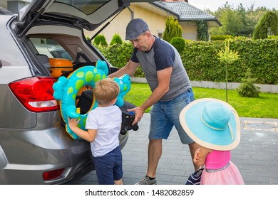 Father with little son and daughter are loading the car trunk with luggages for holidays