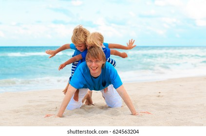 father with little son and daughter play on beach