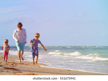 father with little son and daughter run at beach