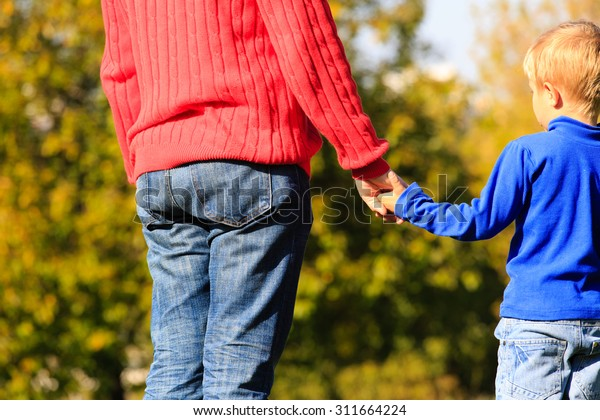 father and little son hands outdoors on autumn day