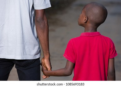father and little son holding hands walking on a road. the father's hand lead his son into the wild with confidence in the outdoors protecting him.the parental concept of parental care. road to life.