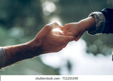 father and little son holding hands in summer sun light. father hand lead his child in  nature outdoor, trust, protecting, care, parenting family concept. road to life. fathers day