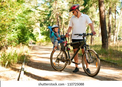 Father and little son on bike with child seat in summer forest