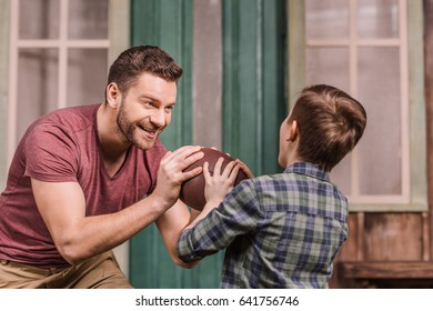 father with little son playing american football with ball at backyard, dad and son playing
