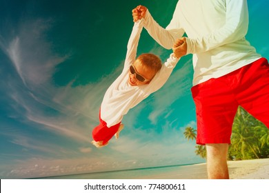 father and little son playing at beach