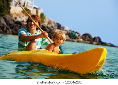 Father with little son rowing on the kayak in the sea