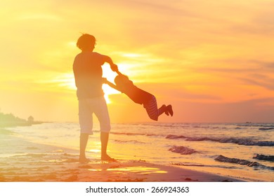 father and little son silhouettes play at sunset