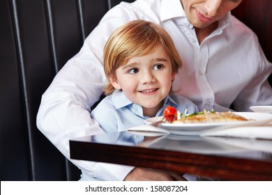 Father and little son sitting together at the dining table