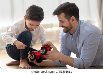 Father and little son spend time together at modern home dad helps to kid with repair works, boy hold screwdriver fix broken truck lorry red car, skills transmitted from one generation to next concept
