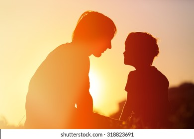 father and little son at sunset sky, family concept