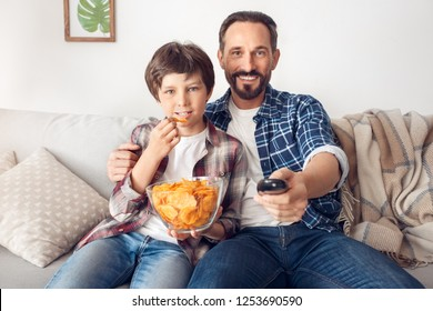Father and little son together at home sitting on sofa boy eating chip watching tv program concentrated dad holding remote controller switching channel smiling joyful
