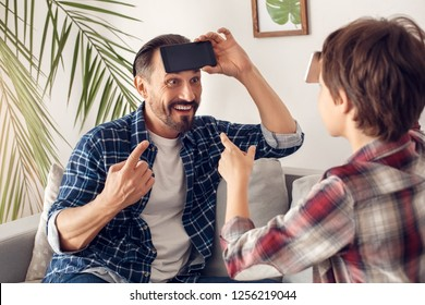 Father and little son together at home sitting on sofa playing heads up using smartphone guessing word smiling cheerful