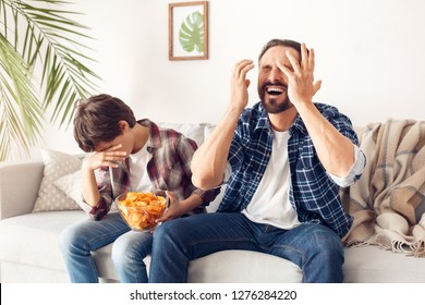 Father and little son together at home sitting on sofa boy holding bowl with potato chip covering face disappointed while father holding hands up shouting unhappy watching football match favorite team