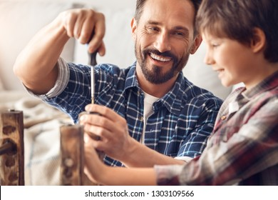 Father and little son together at home standing at table dad screwing screw laughing happy looking at boy holding chair leg teamwork close-up