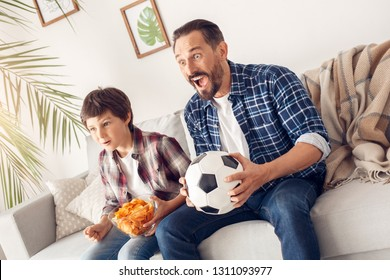 Father and little son together at home sitting on sofa boy holding bowl with potato chip and dad holding ball watching soccer match shouting happy excited.