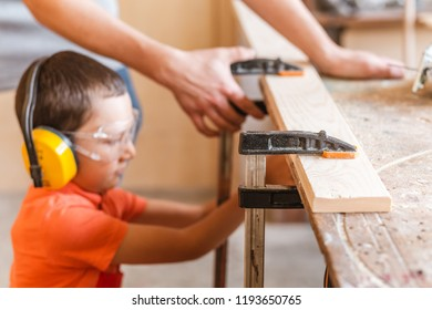 father and little son working together with wood plank at workshop. Carpentry and joinery class concept