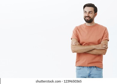 Father looking at son playing on playground feeling proud and happy. Charming adult bearded male with black hair crossing arms on chest in confident and self-assured gesture smiling gazing left