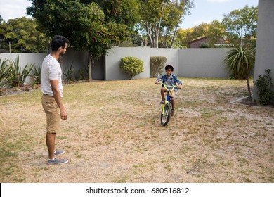 Father looking at son riding bicycle on field in yard