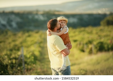 The father lovingly holds his daughter in his arms and hugs her.