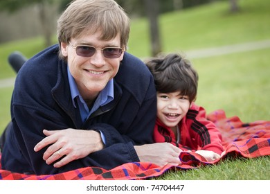 Father lying on blanket with disabled son at park
