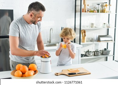 father making orange juice by squeezer while his little son drinking juice at kitchen