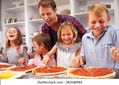Father making pizza with his kids