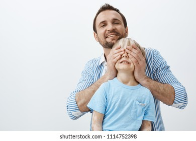 Father making surprise to son on birhday. Portrait of caring loving dad covering child eyes with palms and smiling broadly at camera, wanting to give gift and make great present for cute kid