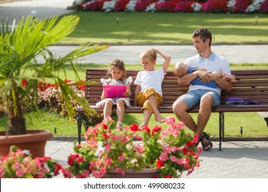 Father of many children for a walk with their children in a summer park. Sit on the bench.