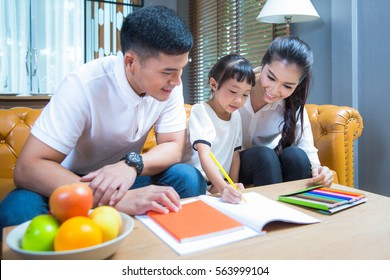 Father and Mather teach and relax with they Daughter  to do home work by draw and paint, family , kid , education concept.