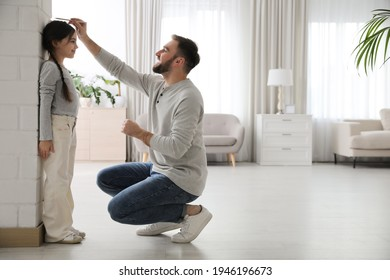 Father measuring daughter's height near white brick pillar at home, space for text