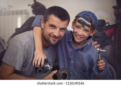 father mechanic with son examining  car at the repair garage
