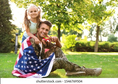 Father in military uniform with American flag and his little daughter sitting on grass at park