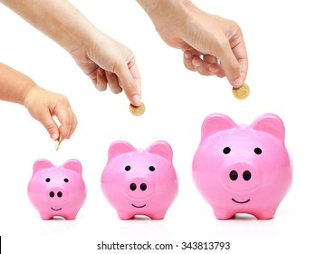 Father, mother, and baby in the family do saving money in pink piggy banks in three different sizes