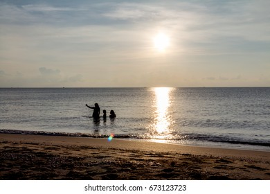 Father, mother, and child Enjoy the sea at dawn.