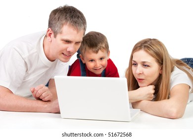 Father, mother and child lying on the floor with laptop