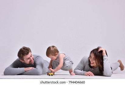 father mother and child on white background, gray clothes, lie on the floor and play with her son.