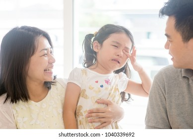 Father and mother  comforting crying daughter. Asian family at home, natural living lifestyle indoors.