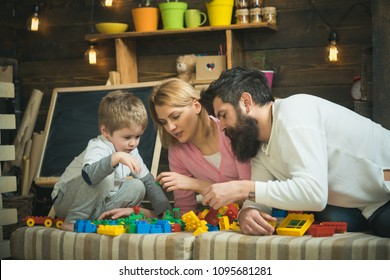 Father, mother and cute son play with constructor bricks. Family on busy face spend time together in playroom. Caring parents concept. Kid with parents play with plastic blocks, build construction.