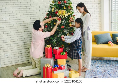 Father, mother and daughter are decorating the Christmas tree. Families celebrate Christmas and New Year's conception.
