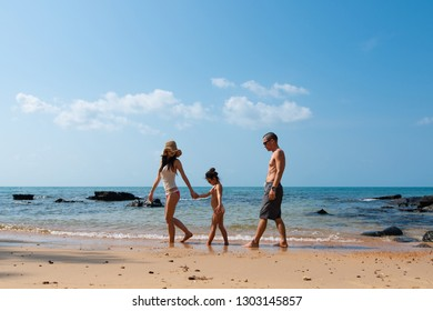 Father and mother and daughter playing on the beach