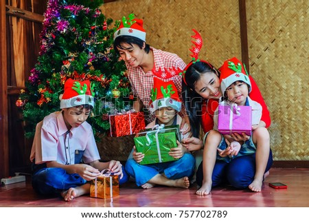 father and mother giving gifts to children in christmas festivalhappy family celebrating on new
