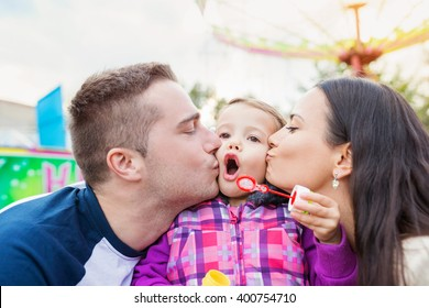 Father, mother kissing their daughter blowing bubbles, amusement
