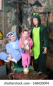 Father, mother and little daughter in colorful costumes of dragons growl and scare in very old room.