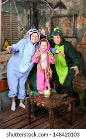 Father, mother and little daughter in colorful costumes of dragons attack in very old room.