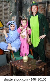 Father, mother and little daughter in colorful costumes of dragons pose in very old room.