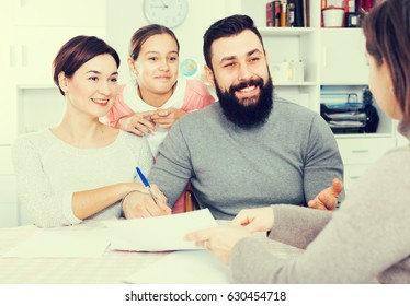 Father and mother preparing property papers with their daughter