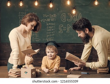 Father and mother reading books, teaching their son, chalkboard on background. Family cares about education of their son. Boy child in graduate cap likes to listening stories. Homeschooling concept