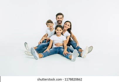 Father, mother, son and cute daughter. Beautiful and happy smiling young family in white T-shirts are hugging and have a fun time together while sitting on the floor and looking on camera.