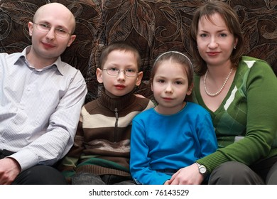 Father, mother, son and daughter sitting on couch and smiling, happy family