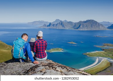 Father, mother and son on a mountain top looking at Norway beautiful view. Lofotens